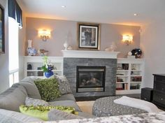 This neutral living room features a gray stacked stone fireplace surrounded by built-in white bookcases. A gray sectional sofa provides plenty of cozy seating while bright green pillows add a pop of color.