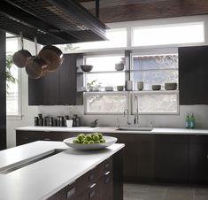 "Modern industrial kitchen. Blackened steel floating shelves. Dark stained oak casework. Doug Mockett tab pull hardware. White quartz composite countertops. Dark stained beams and ceiling panels. Custom trough sink. Dornbracht ""Meta"" faucet."