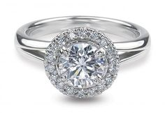 Ritani for Forevermark diamond engagement ring featuring a round halo with a prong set round cut center stone that is surrounded by pavé diamonds and a split metal shank.
