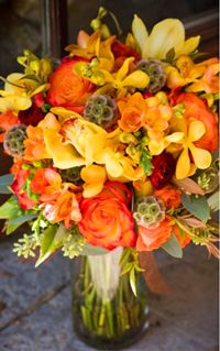 beautiful fall bouquet made of yellow cymbids, scabiosa pods, freesia, roses, mokara orchids and seeded eucalyptus.