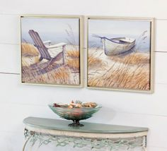 This set of 2 coastal beach canvas art prints feature an Adirondack style chair and a boat sitting among the grasses on the sand next to the shoreline