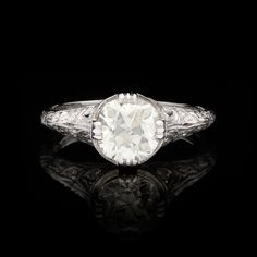 1.48 Carat Old Mine Cut Diamond Accented with 0.21 Total Carats of 12 Round Brilliant Diamonds, Detailed with Filigree & Millgrain in Platinum.