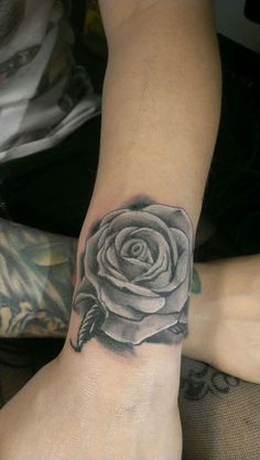 small rose on the wrist black and grey tattoo