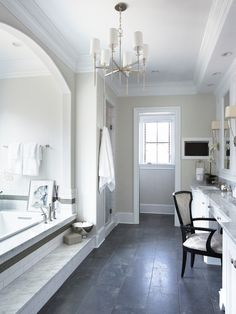 The step treads to the bath are marble with a white tile banded with a gray green stripe on the risers. Dark charcoal gray staggered tiles finish the main floor space. A room length custom white vanity features dual his and hers sinks with a central make up area. The vanity is topped with marble countertops. Above the vanity paneled mirrors are flanked by contemporary wall sconces. An inset flat screen television hangs on the wall at the end of the room.