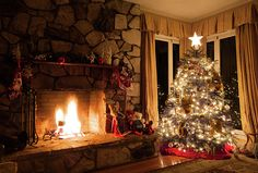 A beautifully decorated Christmas tree, dressed with Christmas tree lights and a star atop, is placed in the corner of a vintage styled model home. A rustic stone fireplace contains a roaring log fire to warm the cozy interior of the home. The room is lit purely by the fire and the Christmas lights to create the warm, romantic and cozy mood.   #Christmas #ChristmasTree #fireplace #cozy #homedecor #xmas