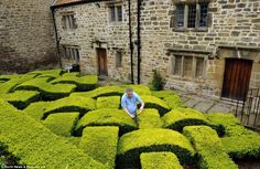 It's a shear delight: Work finally begins on annual trimming of knot garden weaving box hedge at 17th century manor (thanks to a break in the rain)