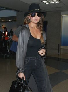 Chrissy Teigen upped her travel beauty game with a thick side plait tucked under a fedora at LAX