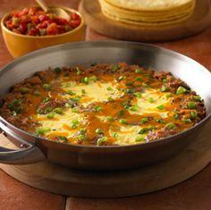 """Suculentos Huevos a la Sartén... Disfrute de un plato principal sin carne, de huevos cocinados en """"tazas"""" de frijoles refritos, cubiertos con queso y sabrosos tomates, servidos sobre tortillas de maíz"""
