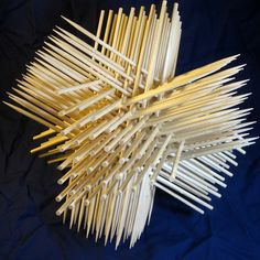 Triskewers — Sculpture by Zachary Abel A subset of an infinite, repeating arrangement of interwoven cylinders, made from 144 wooden skewers and held together with glue. The skewers form four identical, intersecting triangular prisms, giving the figure chiral tetrahedral symmetry—or chiral cubic symmetry if the spiked and non-spiked ends are not distinguished. The high density packing and repetitive lattice pattern create mesmerizing networks of passageways through the sculpture.