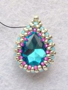 Step by step instructions on how to bead around a pear shaped pendant.