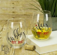 Personalize these Hubby and Wifey stemless wine glasses with your wedding year, or give as a wedding, engagement or anniversary gift. Customize the lettering colors on these 21 oz. wine glasses to reflect your personal style or to indulge a couple you love!  To Order: 1. Select your Hubby/Wifey Lettering Color from the drop-down box. 2. Select your Established Year Lettering Color from the drop-down box. The heart above the i in Wifey will also be changed to this color unless otherwise r...