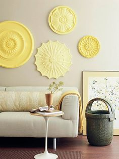 Carved ready-made ceiling rosettes make an impressive eye-level wall display. Painted in graduated shades of yellow, the discs add style to a living room. Made of urethane and available at most home centers for less than $50, they are lightweight and easy to hang