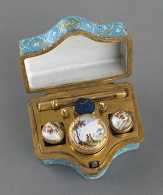Pale blue enamel writing box/etui of rectangular form with projecting waved front side and fitted with gilt metal hinge and scalloped rim mounts. Painted on top and sides with rural scenes reserved by gilt foliate scrolls. Contains pot, inkwells, pencil, nibs and seal.