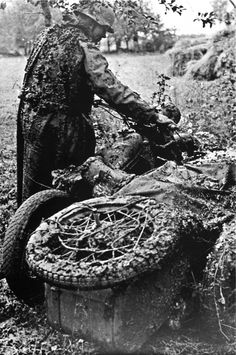 German motorcyclist is pushing his Zundapp KS 750 motorcycle with side car through the muck. Note how his back is covered with mud kicked up by the rear wheel spinning constantly.