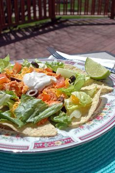 Buffalo Chicken and Nacho Salad - So easy and fun! Throw the chicken in the slow cooker with some hot sauce, shred it, and layer your salad with tortilla chips, cheddar, tomatoes, olives, Ranch & lime juice. Try it with Cooking with Mamma C's homemade Ranch for a low-fat option. #glutenfree