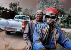 Residents with faces covered in ash ride on a motorcycle as Mount Sinabung volcano erupts, in Sukandebi village in Karo Regency, Indonesia's North Sumatra province, June 13, 2015