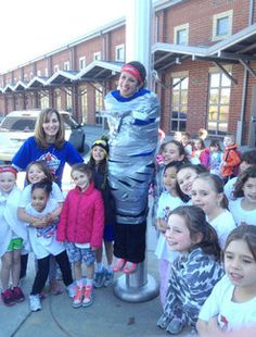 Sugar Creek Assistant Principal Michelle Gritz, is taped to the flagpole in celebration for receiving pledges from all 50 states.