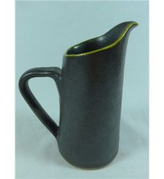 Hand made milk jug by Mervyn Gers. A very attractive milk jug, hand made in South Africa by Mervyn Gers. Decorated in black lustre glaze with yellow glaze to the spout rim. Height to spout lip 16cms, base diameter 8cms.