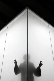 A Hayward gallery worker stands inside Blind Light, a reinforced glass box installation by British artist Antony Gormley, in London on Tuesday.