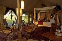 Roar Africa Safari - Sabora Tented Camp: The tents are all furnished in the grand old Hemingway theme with large four poster beds, campaign furniture & writing desks. All the tents are made of brown canvas with a long wooden balcony running along one side that look out towards the east, across the vast plains where the Great Migration flows. www.roarafrica.com