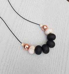 This strikingly stunning piece is designed to add a special touch to your outfit and to make a statement. Each clay bead is rolled and formed by hand. The clay beads and two copper beads are strung on a black coloured genuine leather cord. This necklace is adjustable in length.