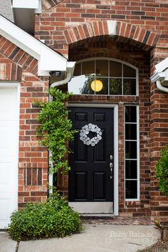 Front door makeover, black door red brick, modern wreath, yarn wreaths are SO not worth the time