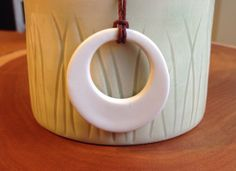 This pendent was hand cut and shaped from porcelain and glazed white. The pendant is strung with burgundy coloured hemp and tied with slip knots for an adjustable length.
