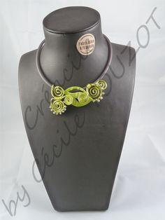 Collier en fil aluminium vert sur tour de cou en caoutchouc gris.   Composé de perles de rocaille grises et d'une grosse perle imitation feuille.   Collier frais et atypique par sa forme et son duo de couleur.   A porter sans modération !