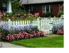 White picket fence with flower beds