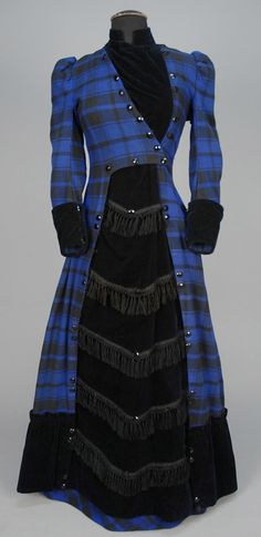 WOOL PLAID AFTERNOON DRESS, c. 1881. Black and blue plaid with black velvet high neck velvet bodice insert, cuff and fringed front panel, with deep ruched hem band