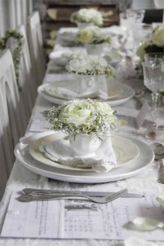 White rose arrangement in a cup at each table setting is so elegant.