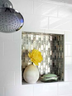 While the majority of the shower is subway tile, this niche get special treatment with glass mosaic tile. One sheet of tile can make a big impact in an all white space.
