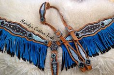 Mandy's Custom Tack and more; $475  tan leather, turquoise/black fringe, black ostrich leather and turquoise ice overlay.