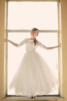bride in tulle dress standing in window sill with long lace sleeves @myweddingdotcom