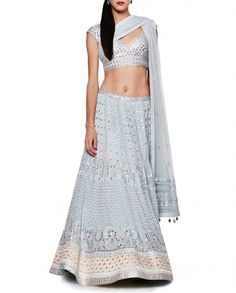 $3260 Powder blue Lehenga comprising a powder blue choli with silver gota patti and dori work all over featuring a plunging V neckline with a princess panel design. Short sleeves. Cut out back design with a drawstring detailed with beads and pompoms. Hook closure at the back. This Lehenga set comes with a powder blue Lehenga skirt with silver gota patti, dori and resham work all over. Golden and silver embellished border. Wash Care : Dry Clean Only. Matching embellished net dupatta included.