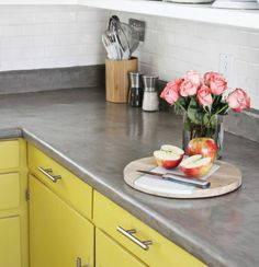 Concrete counter top with yellow cabinets. Great post on kitchen counter tops.