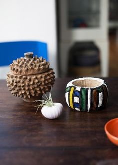"""A collection of mementos picked up on travels. An artist made the bracelet in Nigeria, and the rough knobby ceramic piece is a juju jar from Ghana: """"It's for good vibes!"""" Neal explains."""
