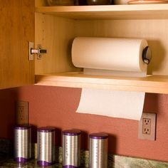 A simple idea--mount the paper towel holder inside the wall cabinet near the sink. Cut a slot in the bottom of the wall cabinet and pull the end of the roll through. Shut the door; the roll is hidden, yet the end of the roll is easily grabbed. We use an eccentric holder. I.e., the bar is not round. That makes it easy to tear off a sheet.
