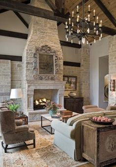 Prominent fireplace - Living room from Design House, Houston TX. High ceilings with dark beams, large chandelier, fireplace. Rustic Fireplaces, Farmhouse Fireplace, Rustic Farmhouse, Stone Fireplaces, French Country Fireplace, Living Room Fireplace, Limestone Fireplace, French Country Living Room, Outdoor Fireplaces