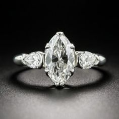 A gorgeous, bright white, classically cut marquise diamond, weighing 1.62 carats, sparkles between a matched pair of old mine-cut pear shape diamonds in this absolutely stunning three-stone engagement ring, hand-fabricated in platinum. The scintillating center stone boasts a beautiful voluptuous cut, characteristic of fine stones fashioned during the 1930s. A truly elegant and superlative vintage jewel. Currently ring size 6.