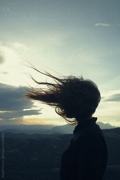 Girl's silhouette with her long hair blowing in the wind  by Miquel Llonch