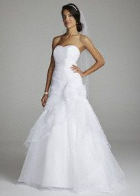 Fairytale romance meets contemporary chic for a flawlessly stunning result! This strapless organza gown features an ultra-feminine sweetheart neckline that is right on trend. Side draped bodice is adorned with a sensational 3D floral accent. Full dramatic skirt and lace up back finish off the look. Chapel train. Available in White. Fully lined. Lace up back. Imported polyester. Dry clean.This neckline is shaped like the top of a heart and is flattering to the decolletage.Train that extends…
