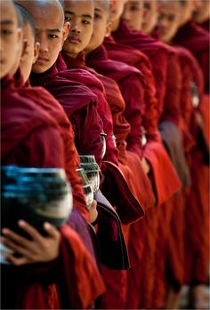 """A selected monk-Rice bowls and their attendant monks wait in line for the offerings from the community neighbouring the Chaukhtatgyi Monastery in Amarapura in Myanmar ahead of the morning meal."" by Christopher Martin"