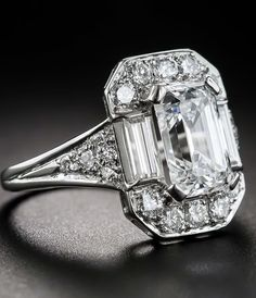 A classically modeled, vintage emerald-cut diamond, weighing just shy of two-and-a-half-carats and bearing a GIA Diamond Grading Report stating: E color-VS1 clarity, is presented in consummate Art Deco style in this stunning and impressive platinum and diamond ring. The icy-white diamond, presumably cut during the 1930s-40s, was evidently remounted at a later date utilizing modern full-cut and sleek straight baguette diamonds on top and the original european-cut diamonds on the sides.
