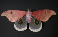 This moth is about 4 1/2inches tall and 10 1/2 inches wide. The wings are made from cotton fabric and the body is made from fake fur.  It is hand painted and hand embroidered with details. The antennas is made from feather. There is metal hook on the underside for hanging.