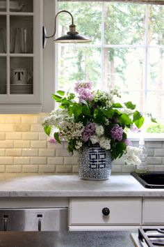 kitchen with marble counters, glass-front cabinets, lilacs in blue + white porcelain. Love the vintage barn light sconce and the backsplash.