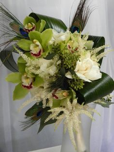 upright bouquet of cymbidium orchids, astilbe, peacock feathers and aspidistra leaves