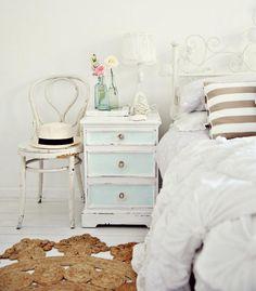 chambre bohème blanche avec une table de chevet et une chaise de style shabby chic, tapis sisal en forme de soleil et déco florale