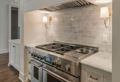 Beautiful kitchen with shiplap paneling concealing a vent hood which stands over a gray subway marble tile backsplash lit by Reed Single Sconces and a stainless steel stove.