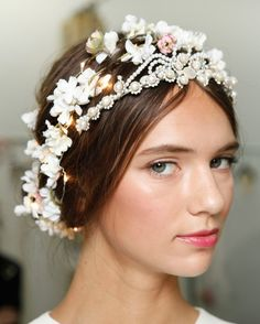 Seen at: Reem AcraJoseph DiMaggio, master session ambassador for Davines North America, achieved this subtly glowing bohemian hairstyle with a braided bun, winding flowers, and an ingeniously hidden LED battery pack.